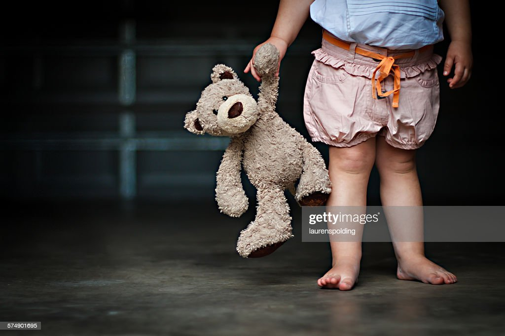 Low section of a girl holding her teddy bear : Stock Photo
