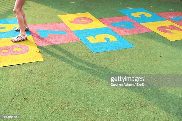 low section of a girl playing hopscotch - hopscotch stock pictures, royalty-free photos & images