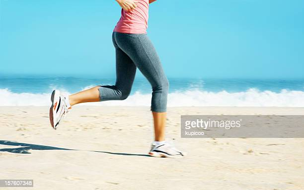Low section of a lady jogging on beach