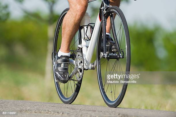 Low section of a man cycling on road