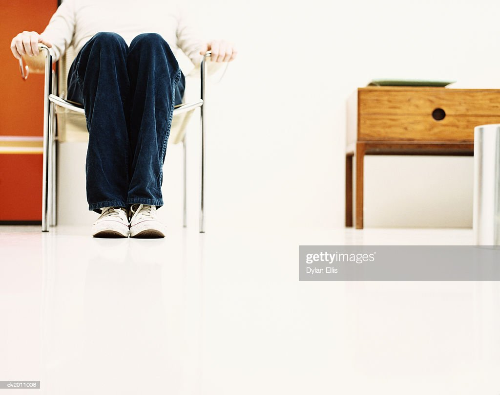 Low Section of a Man Sitting in a Chair Indoors, Surface Level : Stock Photo