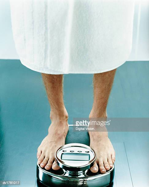 Low Section of a Man Standing on a Pair of Scales