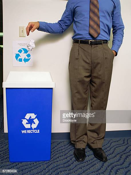 Low section of a man throwing a paper in the dustbin
