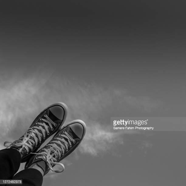 low section of a man wearing red canvas shoes against sky - hainaut stock pictures, royalty-free photos & images