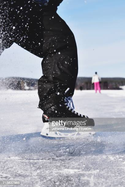Low Section Of A Person Ice Skating On Frozen Lake