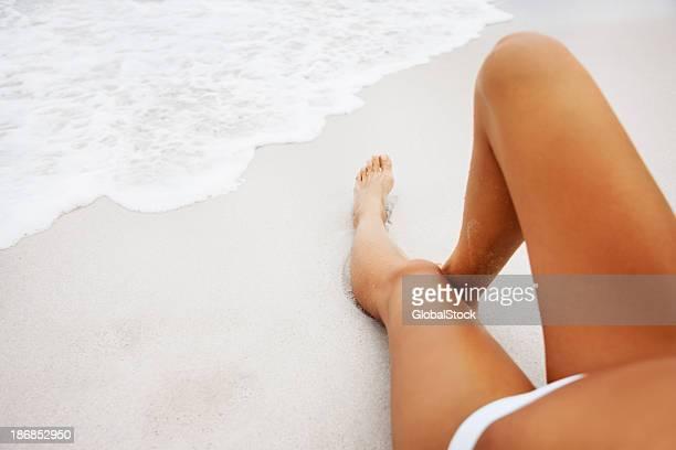 Bajo la sección de una sexy mujer descansando en la playa