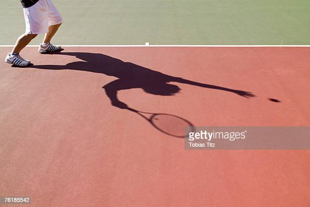 Low section of a tennis player and his shadow
