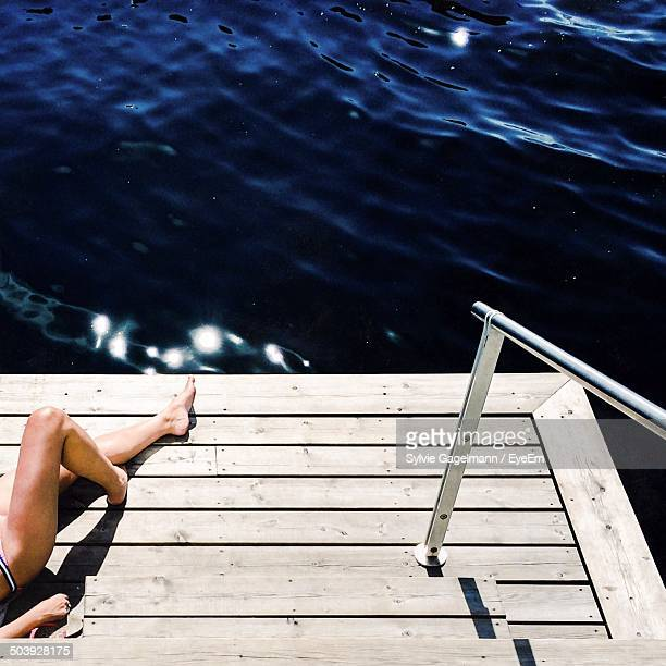 Low section of a woman lying on wood paneled surface by the sea