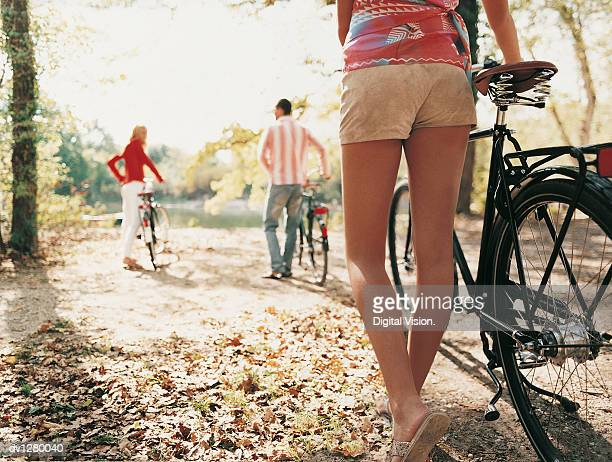 low section of a woman pushing a bike and a couple pushing bikes in the background - lake bottom stock photos and pictures