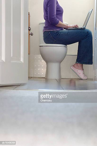 low section of a woman sitting on a lavatory using a laptop - human toilet stock-fotos und bilder