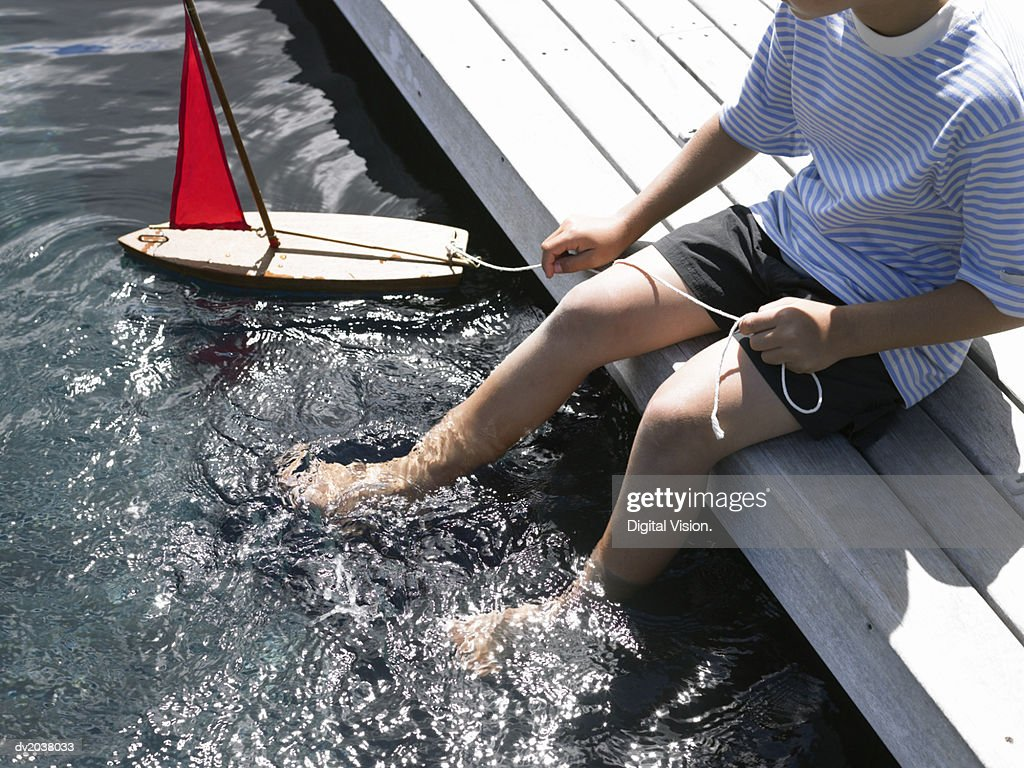 Low Section of a Young Boy Sitting on a Promenade Playing With a Toy Boat : Stock Photo