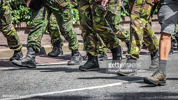 Low Section Of Army Soldiers Walking On Road