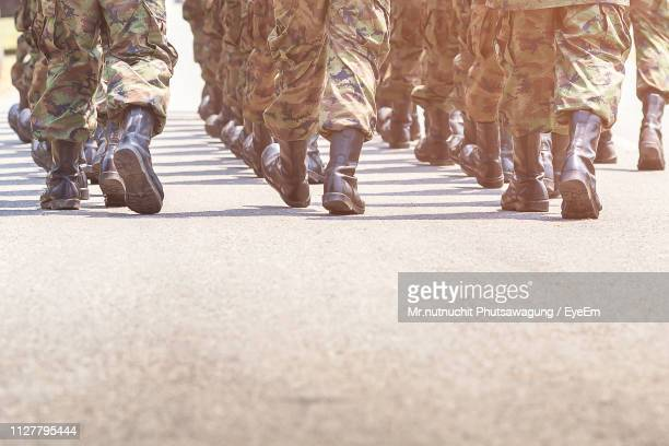 low section of army soldiers walking on street during parade - army stock pictures, royalty-free photos & images