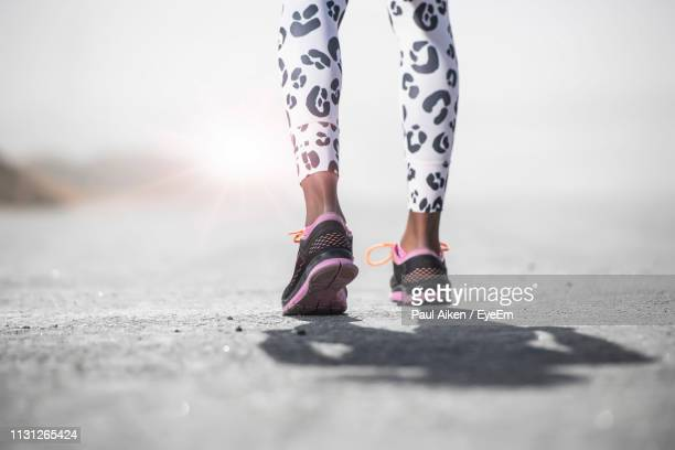 low section of athlete exercising on road during sunny day - arab feet photos et images de collection