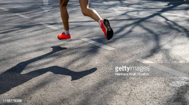 low section of athlete running on road in city - maratona foto e immagini stock