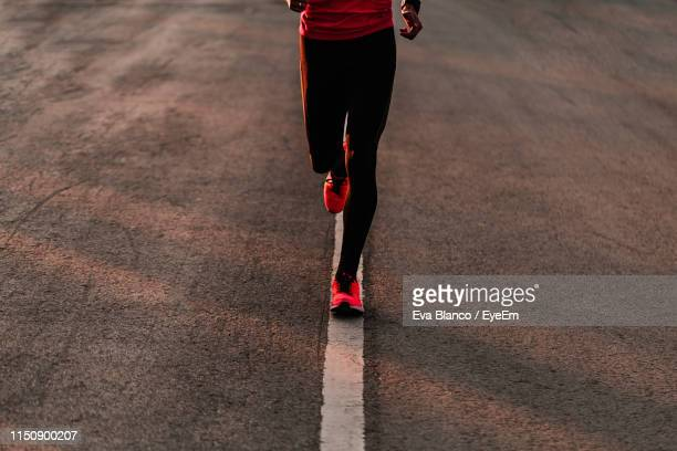low section of athlete running on road - running stock pictures, royalty-free photos & images