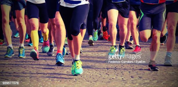 low section of athletes running marathon on road - maratona foto e immagini stock