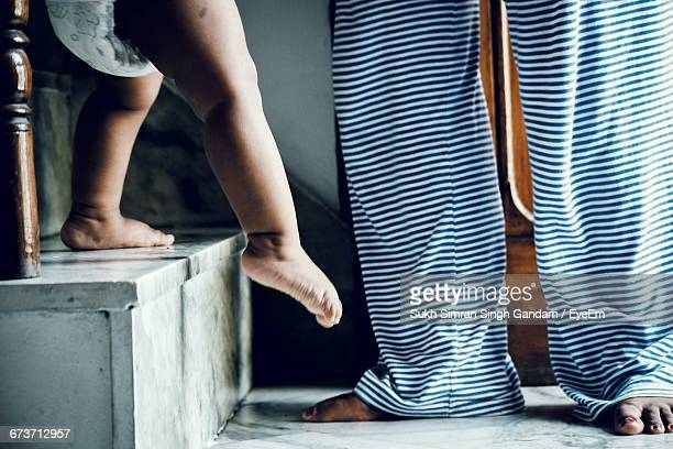 Low Section Of Baby Girl Moving Down Steps While Mother Standing At Home