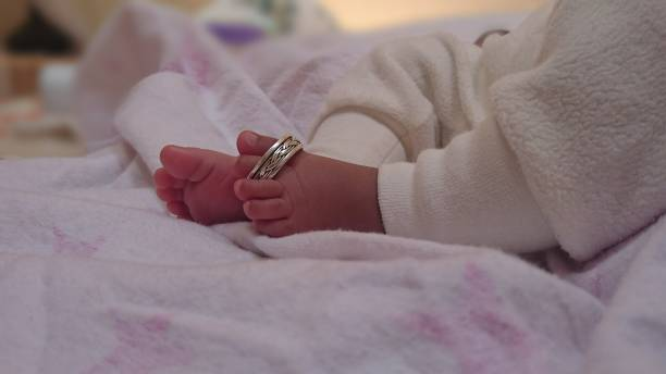 Low Section Of Baby Woth Jewelry On Bed