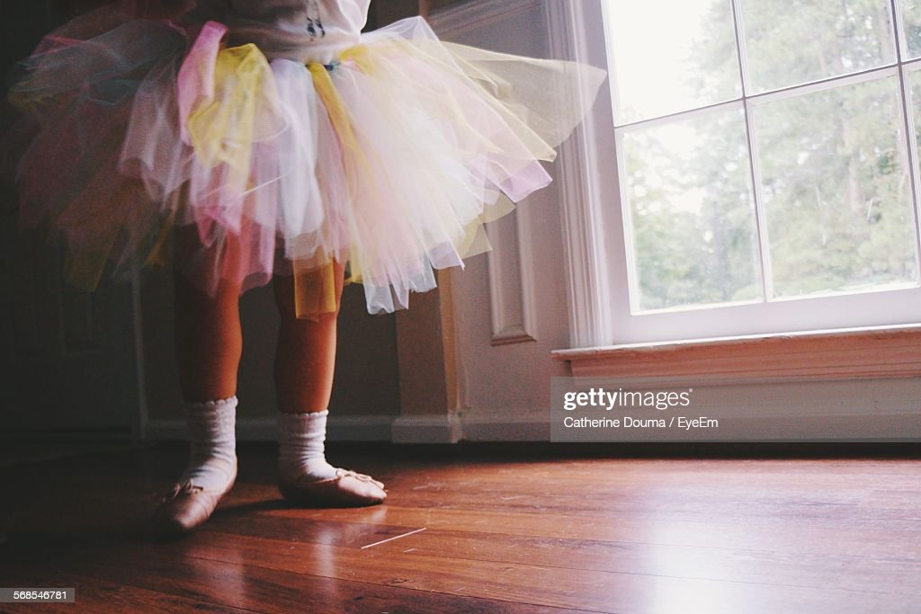 Low Section Of Ballerina Standing On Hardwood Floor At Home : Stock Photo