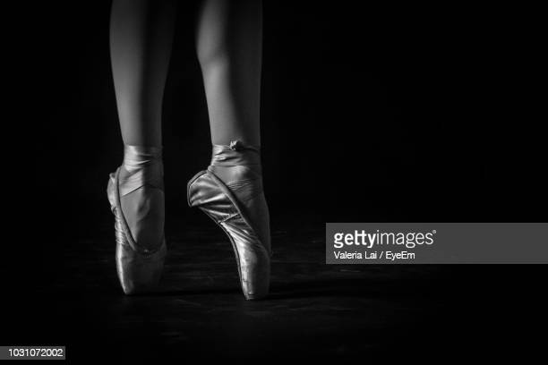 low section of ballet dancer against black background - ballet dancer stock pictures, royalty-free photos & images