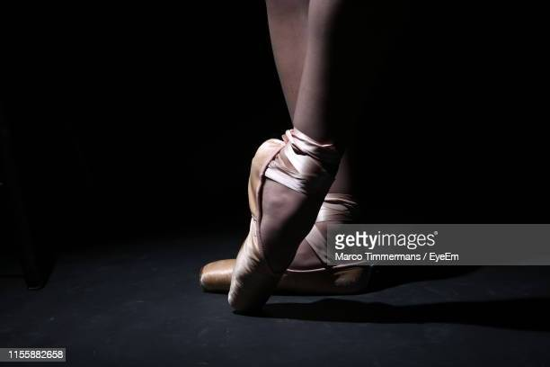 low section of ballet dancer dancing against black background - ballet dancer stock pictures, royalty-free photos & images