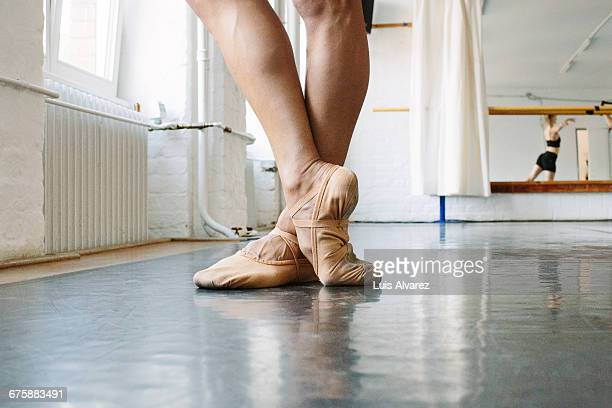 Low section of ballet dancer standing at studio