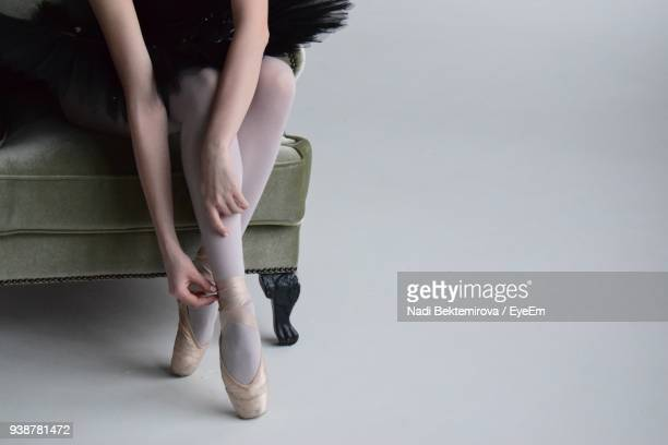 low section of ballet dancer wearing shoe while sitting on sofa - femininity stock pictures, royalty-free photos & images