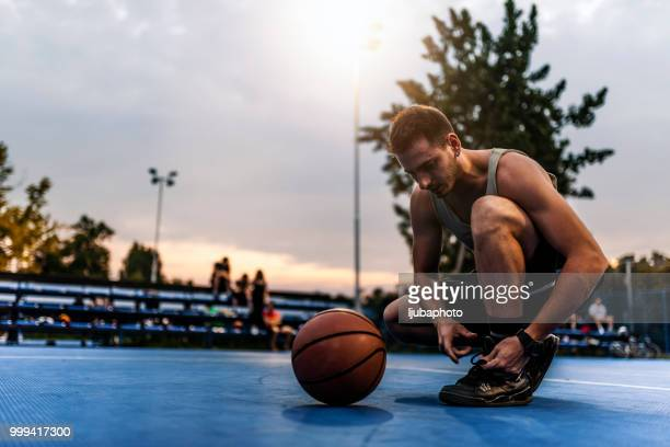 low section of basketball player tying shoelace - basketball shoe stock photos and pictures