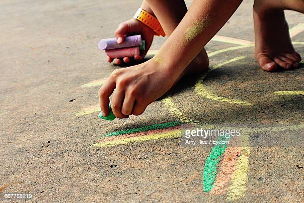 Low Section Of Boy Drawing With Chalk On Street
