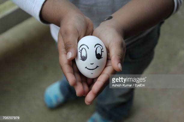 Low Section Of Boy Holding Anthropomorphic Face On Egg