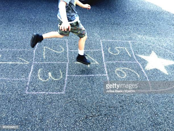 low section of boy jumping on hopscotch - hopscotch stock pictures, royalty-free photos & images