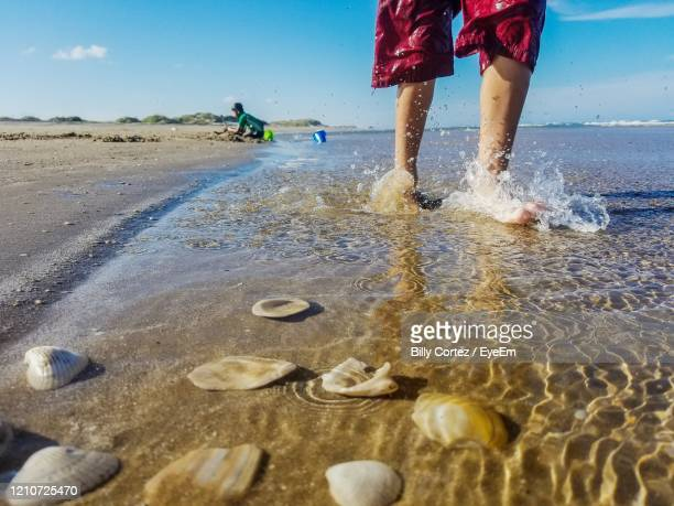 low section of boy on beach splashing against sky - south padre island stock pictures, royalty-free photos & images