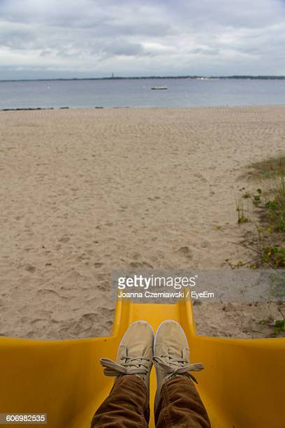 Low Section Of Boy On Slide At Beach Against Cloudy Sky