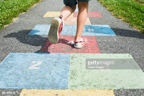 low section of boy playing hopscotch on road - 16:9 ストックフォトと画像