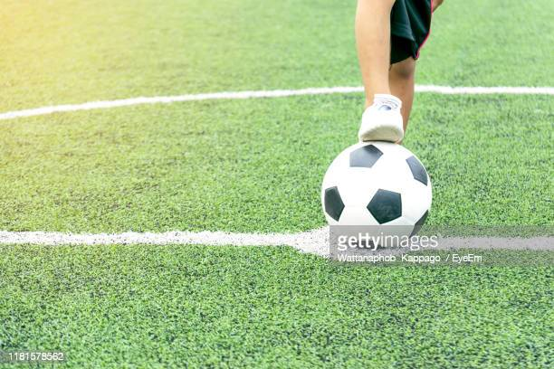 low section of boy playing soccer on land - sode stock-fotos und bilder