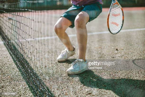 low section of boy playing tennis in sunny day - racquet stock pictures, royalty-free photos & images