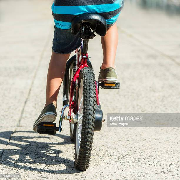 Low section of boy (6-7) riding bicycle