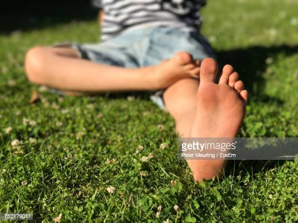 Low Section Of Boy Sitting On Field At Park