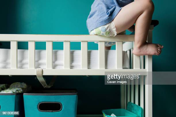 Low section of boy sitting on railing in bunkbed
