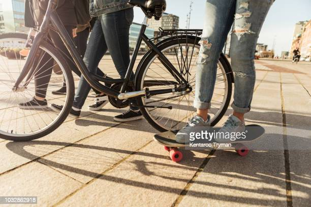 low section of boy skateboarding with friends and bicycle on footpath - trail of tears stock photos and pictures