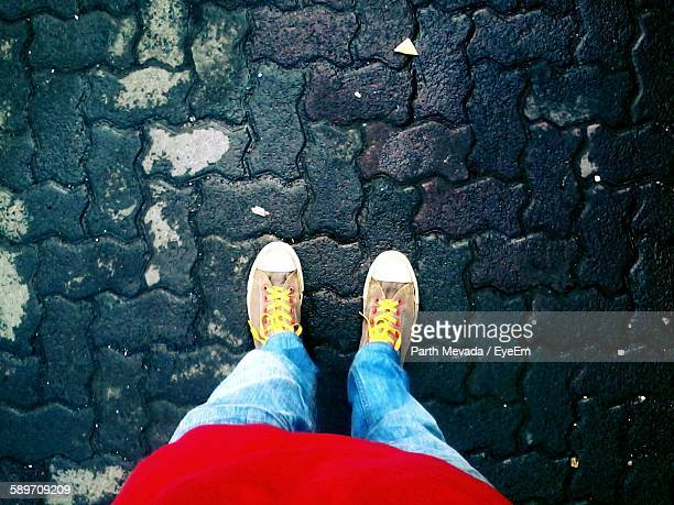 Low Section Of Boy Standing On Paving Stone Street