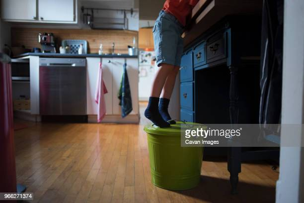 Low section of boy standing on tiptoes reaching for something at home