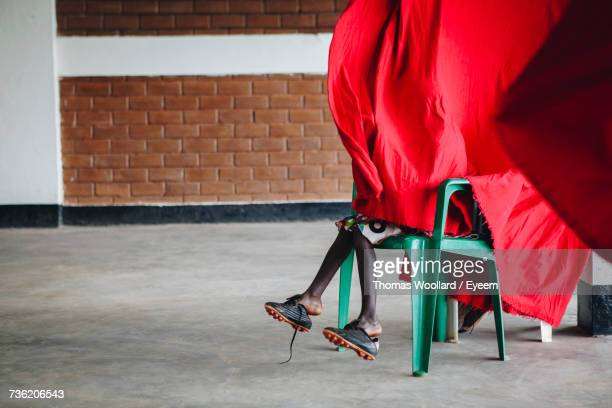 Low Section Of Boy Wearing Shoes Hiding Behind Red Curtain While Sitting On Chair