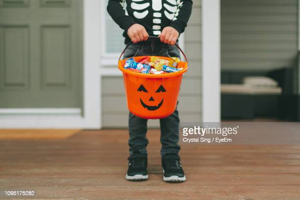 low section of boy with sweet food in bucket standing at home during halloween - halloween stock photos and pictures