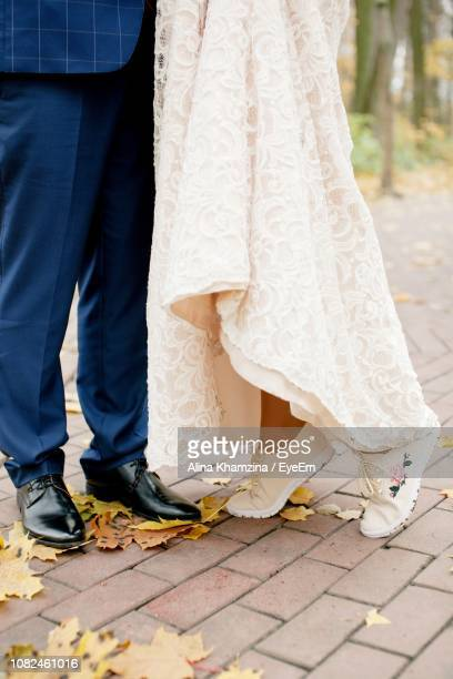 Low Section Of Bride And Bridegroom Standing On Footpath