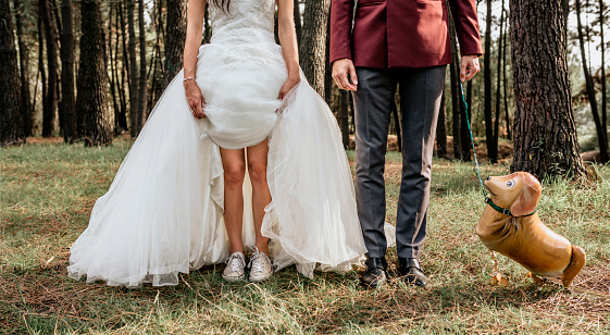 Low section of bride and groom in forest with funny dog-shaped balloon - gettyimageskorea