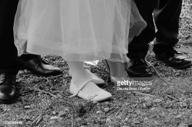 low section of bride and groom standing on field - claudia marie photos et images de collection