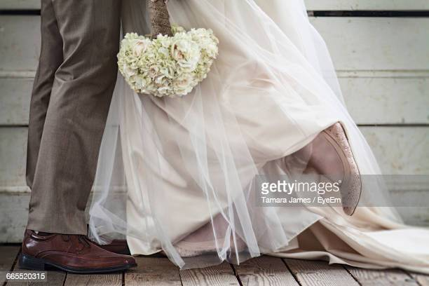 Low Section Of Bride And Groom With Bouquet During Wedding Ceremony