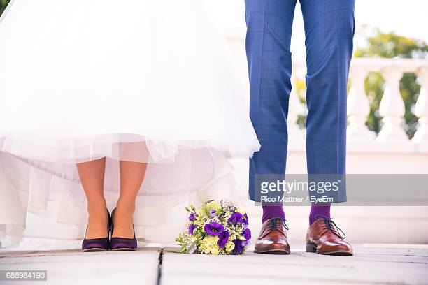Low Section Of Bride And Groom With Flower Bouquet Standing On Floor